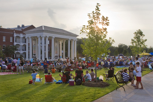Families arrange chairs and blankets on the lawn to enjoy a concert.