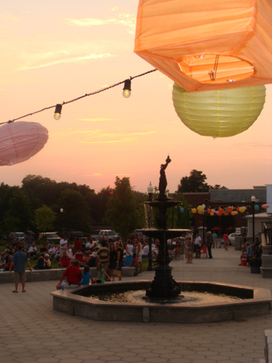 People walk the central walk beneath paper lanterns.